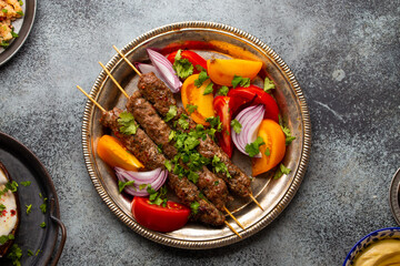 Delicious meat kebab with fresh vegetable salad served on rustic plate, traditional Middle eastern dish. Tasty and healthy meal of Arab or Mediterranean cuisine, from above