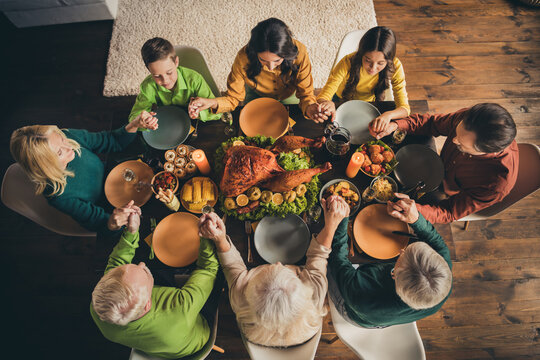 Top above high angle view of nice attractive peaceful thankful family sitting around served table praying god saying grace appreciate domestic meal at modern loft industrial wooden interior house