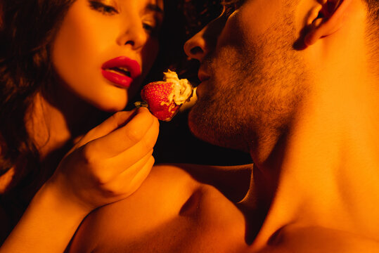 sexy woman with red lips feeding shirtless man with whipped cream on fresh strawberry