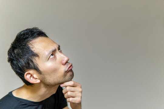 難しい顔をして何かを考える日本人男性