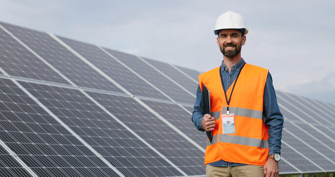 Portrait of electrician in safety helmet and uniform on background field of photovoltaic solar panels. Male technician at solar station.