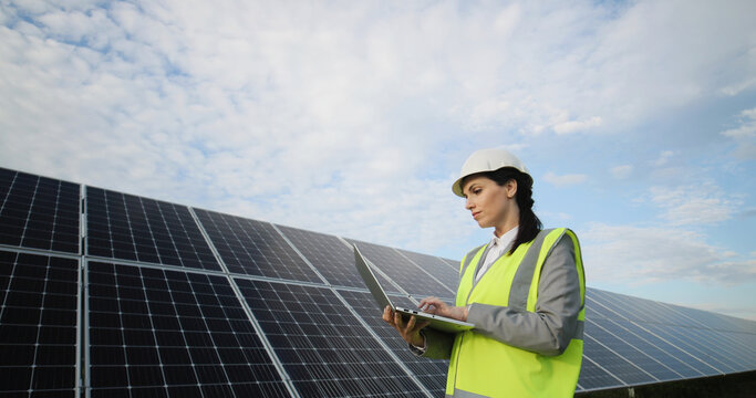 Portrait of electrician engineer in safety helmet and uniform using laptop checking solar panels. Female technician at solar station.
