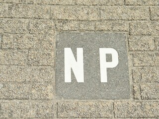Concrete slab set in a gray environment on which the letters NP are attached in white paint. Abbreviation stands for not parking, the letter combination can be used for it in English, German and Dutch