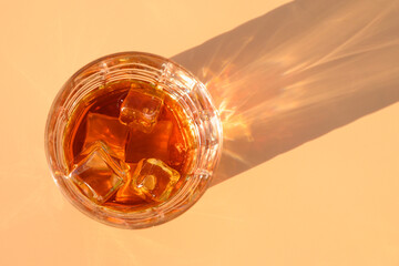 Poster Bar Glass of cold whiskey on beige background with sunny shadow.