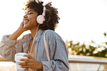 Smiling young african american woman listening to music