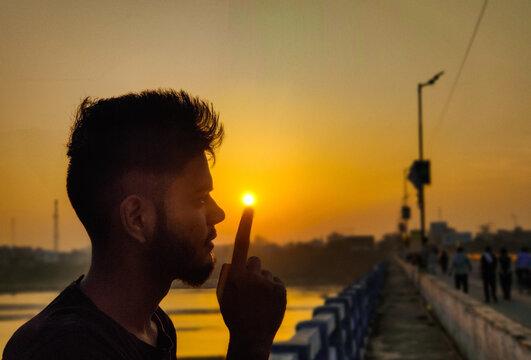 Optical Illusion Of Man Holding Sun At Bridge During Sunset