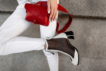 Female legs in white jeans with a red handbag and fashionable shoes sits on the street.