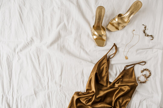 Sexy fashion concept with women's clothes and accessories. Golden shoes, brown silk dress, golden necklace, bracelet, earrings on white linen. Flat lay, top view minimal feminine vogue background.