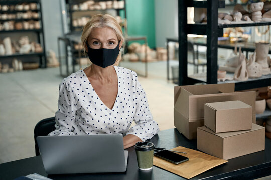 Portrait of female business owner or businesswoman wearing protective face mask using laptop and looking at camera while working in her art studio or craft pottery shop