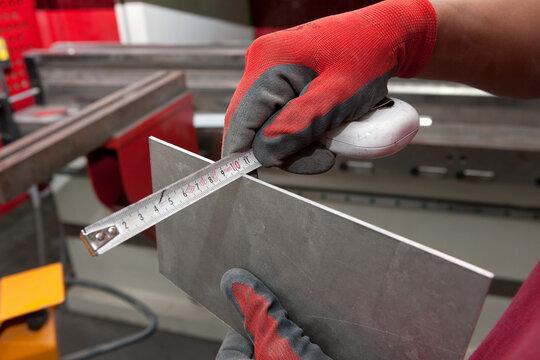 Measuring a piece of metal. Ship building industry. Shipyard. Building superyachts.