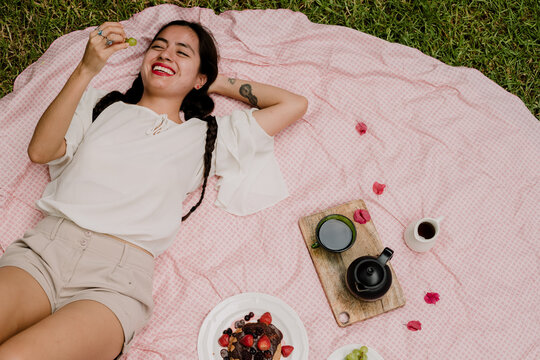 High Angle View Of Woman Having Fruit While Lying On Picnic Blanket In Yard