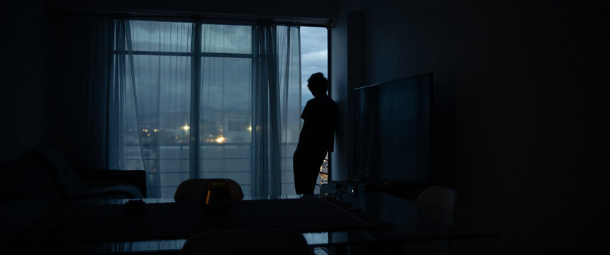 Side View Of Silhouette Man Standing By Window At Home