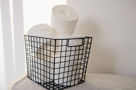Toilet paper rolls storage in a black metal basket on a white background. Minimal interior design concept