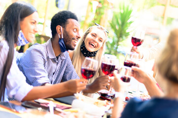 Multiracial group of friends enjoying a wine in a restaurant