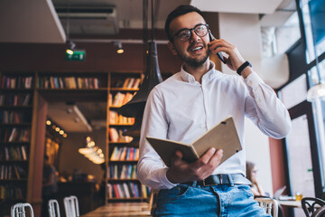 Smiling entrepreneur with book talking on smartphone