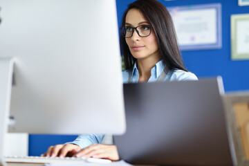 Woman in glasses and blue shirt sit at workplace and look at computer screen. Worker press his fingers on button of white keyboard at table.