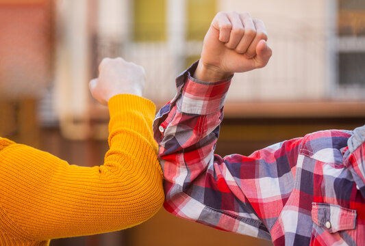 Don't shake hands. Stop handshakes. Elbow bump. Bump elbows. Friends shaking elbows outdoors. Elbow greeting style. Coronavirus epidemic