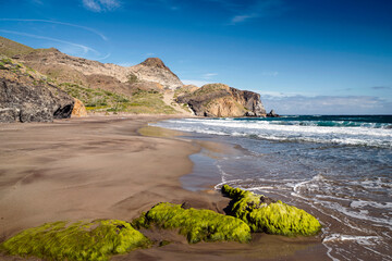 Moss covered rocks on Barronal Beach, Cabo de Gata, Almeria, Andalusia, Spain