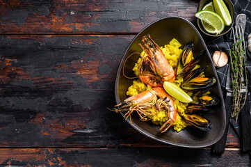 The Spanish Seafood paella with prawns, shrimps, octopus and mussels.  Black wooden background. Top view. Copy space