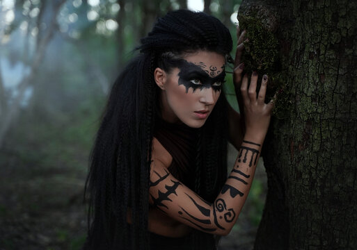 Portret close up of beautiful tribal shaman woman in a foggy forest.Amazon girl near the tree. Soft focus