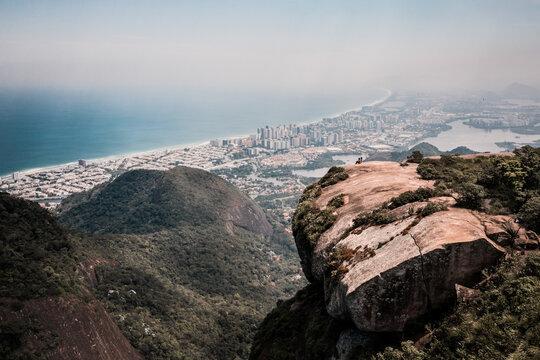 Aerial View Of Two People Sat Upon Pedra Bonita Rock With Barra Da Tijuca In Distance, Rio De Janeiro, Brazil