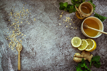 honey, lemon, mint, ginger, oatmeal with a spoon - home remedy to prevent colds on a gray background