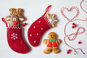 Christmas background postcard, red socks for a gift with gingerbread deer, gingerbread man,  red and white rope on a white wooden table.