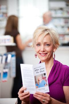 Pharmacy: Woman Reading Flu Shot Brochure