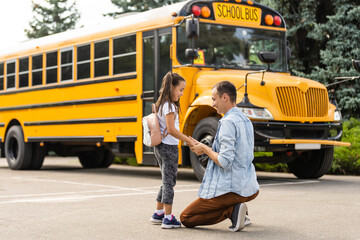 Girl with father going back to school near the school bus