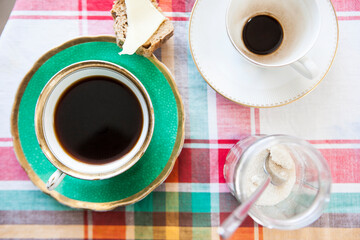 Coffee cups and light snack from above on checkered tablecloth