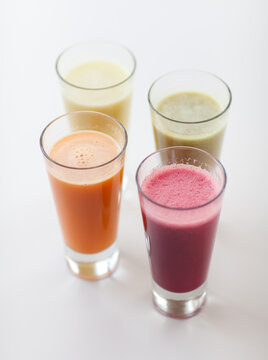 Colorful fruit smoothies on a white table.