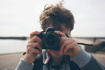 Young guy taking a photo with his camera Papier Peint