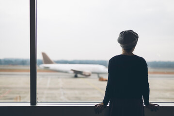 Woman looking an airplane at airport