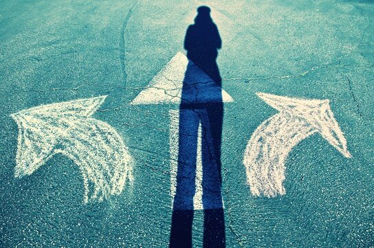 A person looks at three arrows and tries to choose the right path.