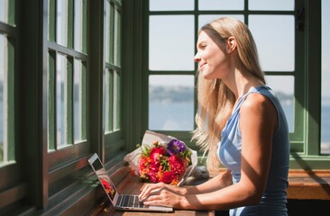 Woman using laptop at window