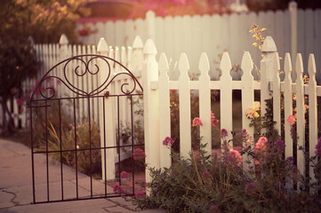 Dreamy sunlit garden with white picket fence and decorative gate