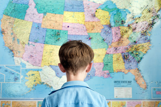 Boy stands looking at a map of the United States