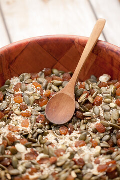 Nuts, seeds and raisins mixed in a wooden bowl.