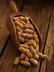 Scoop of peanuts on wooden texture
