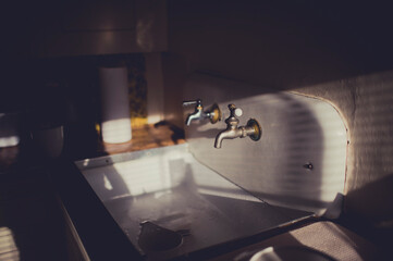 Vintage sink with two taps in afternoon light