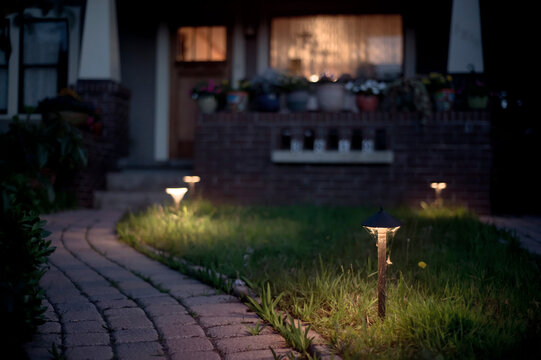 A lighted brick path leading to a house with glowing windows at night