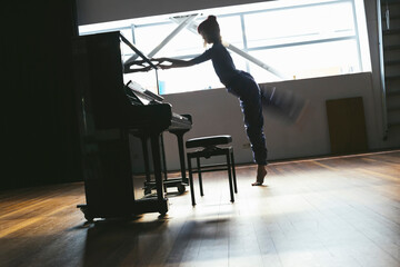 Dancer girl performing against a piano