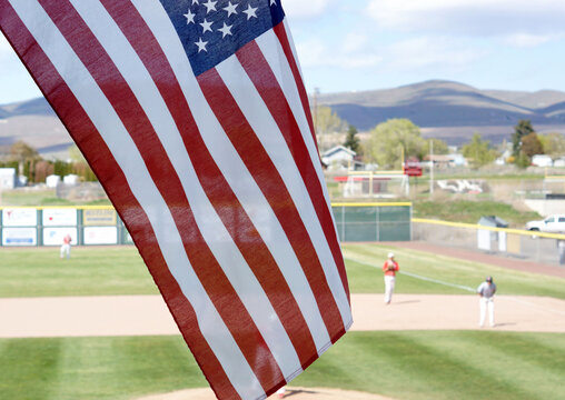 The American flag waving with a rural town's baseball game in the background.