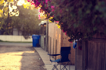 Blue folding chair in sunny alley