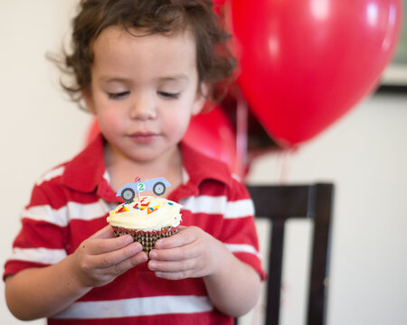 boy eyes a cupcake on his second birthday
