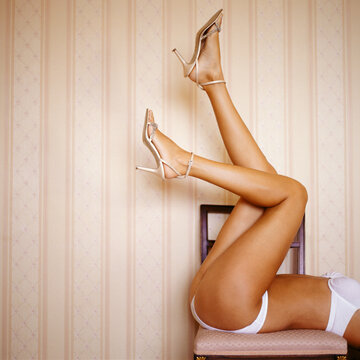 Woman lying on chair kicking her legs in the air.