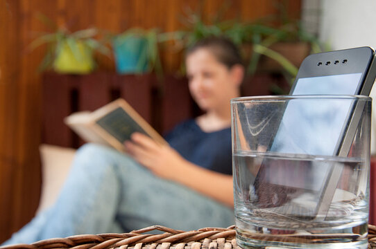 digital detox_smartphone_glass with water_woman reading_by jziprian