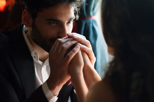 Young man kissing woman's hand.
