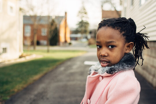 African American girl wearing a pink coat