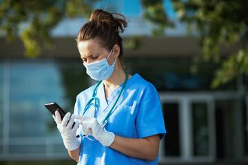 sad modern physician woman using phone app outside near clinic